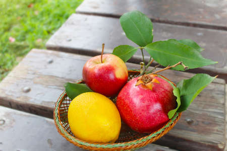 Various fresh fruits in basket on the on vintage wooden planks: pomegranate, orange, apple. Concept gifts of nature