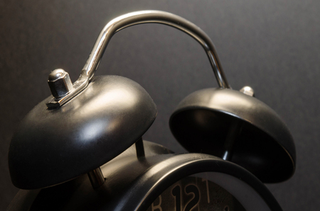 Alarm clock on black background Фото со стока