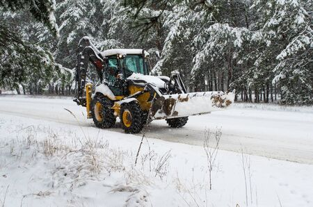tree removal service: Snowblower tractor on road Stock Photo