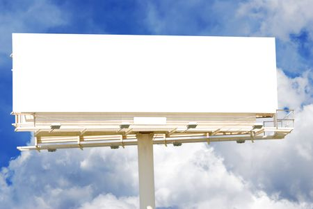 Blank billboard against a partly cloudy sky.