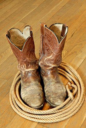 nicked: Maltratadas viejo vaquero y botas lariat piso en madera dura.  Foto de archivo