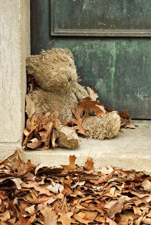 Teddy bear guarding an old vault in a cemetery.