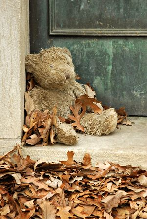 Teddy bear guarding an old vault in a cemetery.