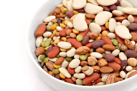 A bowl of mixed dry beans with a white background. photo