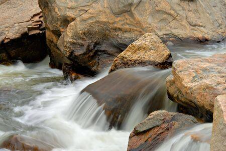 A small cascade flowing over rocks in Colorado.