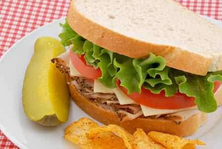 A turkey and swiss sandwich on white bread. photo