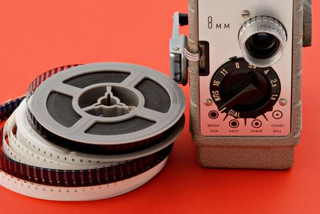 Old 8mm movie camera with film reels on a bright red background. Stock Photo - 2633808