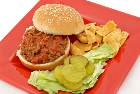 sloppy: A sloppy joe sandwich with lettuce, pickles and chips on a red plate.