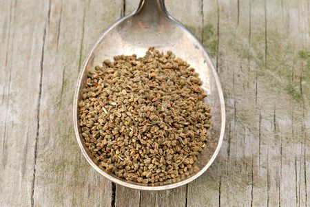 tarnished: Celery seed in a tarnished silver spoon on a rustic wooden board. Stock Photo