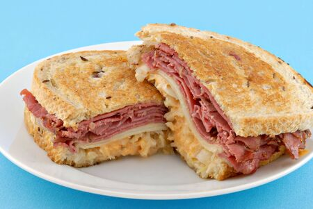 Grilled Reuben sandwich on a textured blue background.