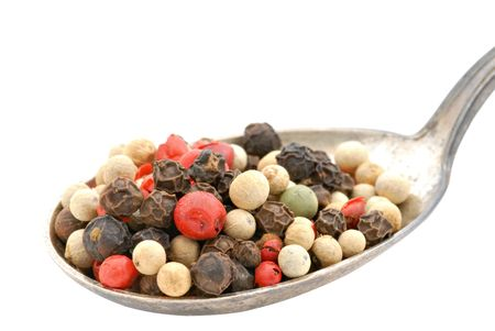 tarnished: A spoonful of colorful peppercorns in a tarnished spoon.