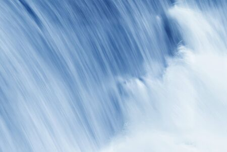 turbulent: Swiftly moving waterfall in shades of blue.