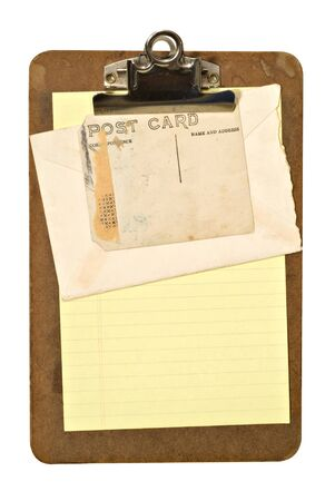 old envelope: An old stained clipboard holding an envelope and old postcard. File has path.