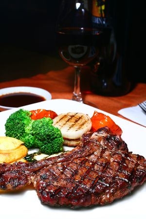 grilled t-bone steak with grilled veggies and red wine photo