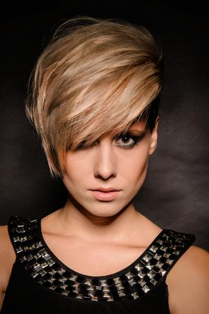 Close-up d'une fille avec une coupe de cheveux courte. Fond sombre Banque d'images - 71533958