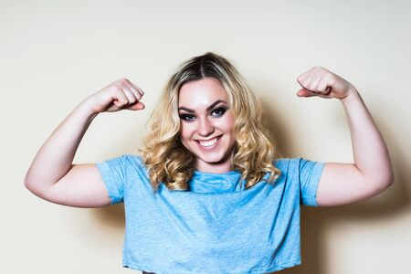 Blonde woman on a light background shows a biceps. Close-up Stock Photo