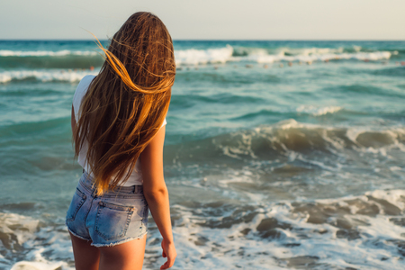 Girl With Long Hair on the background of the sea sunset  close up