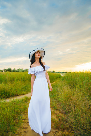 Woman in a white dress on an asshole in a green field Stock fotó
