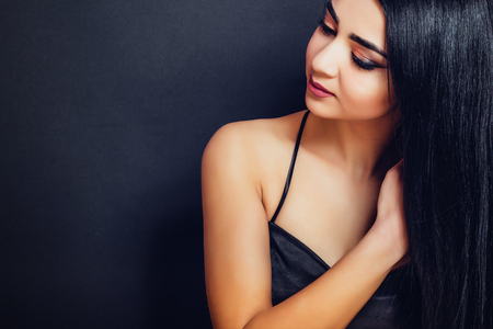 Beautiful brunette girl with black hair on a dark background close-up Banque d'images - 110896158