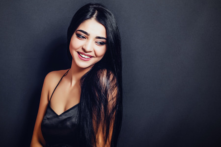 Beautiful woman with black straight hair on a dark background smiling. Close-up. Space for text Banque d'images - 110896162