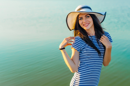 Woman in hat and striped dress on sea background smiling Banque d'images - 110896163