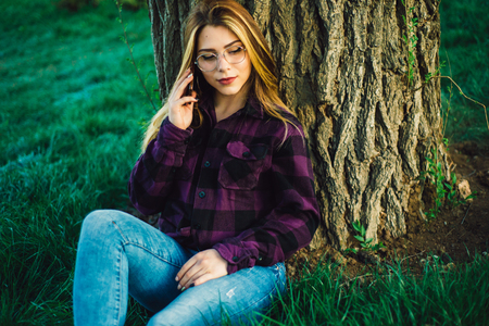 Blonde girl near a tree talking on the phone close up Banque d'images - 100371150