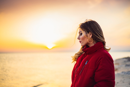 Blonde girl on background of the sea and beautiful sunset close up Banque d'images - 100371152