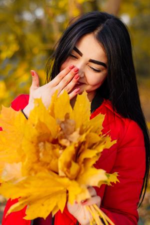 Beautiful brunette woman in autumn foliage smiling. Banque d'images - 110896212