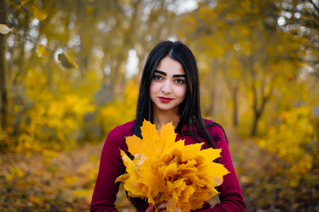 Beautiful brunette woman in autumn foliage smiling. Banque d'images - 110896254