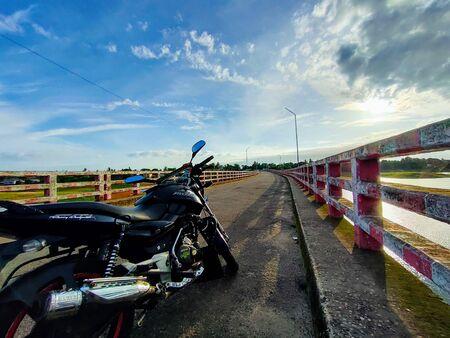 A black bike above the bridge.