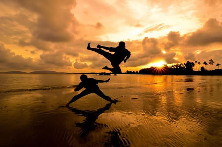 Two friends fight each other near the beach when the sun goes down photo