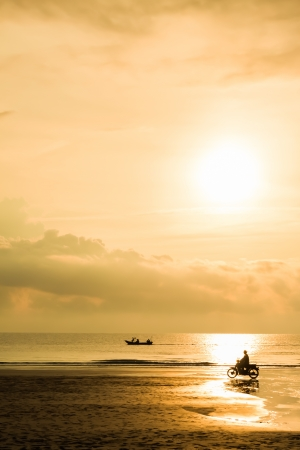 Fishing boat sunrise with motorcycle near the beach photo