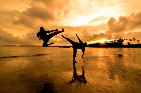 Dos amigos que luchan entre s�, cerca de la playa cuando el sol se pone photo