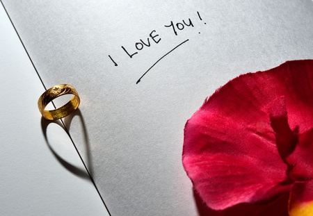 Ring with heart shadow and I love you text with rose on white plain book photo