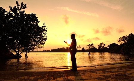 Man praying near beach when sunset photo