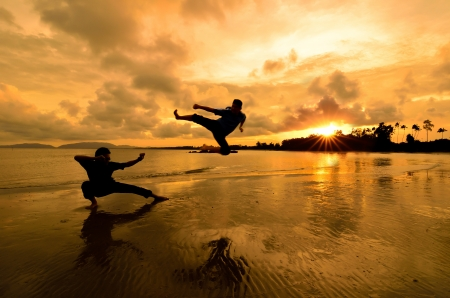 chi: Fighting an enemy near the beach when the sun goes down Stock Photo