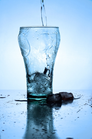 Glass of pouring water with ice photo