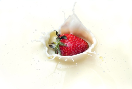Strawberries splashing in to milk photo