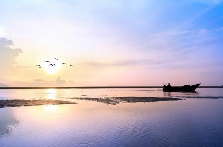 Barco de pesca en la salida del sol con el pájaro volando alrededor Foto de archivo - 20180255