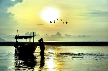 Fishing Boat at Sunrise with bird flying around Stock Photo - 20180242