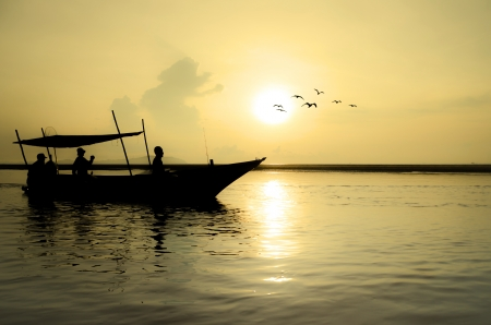 Fishing Boat at Sunrise with bird flying around photo