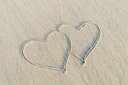 Hearts drawn on the sand of a beach photo