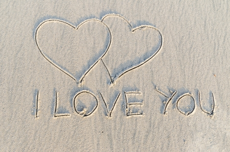 Hearts drawn with i love you text on the sand of a beach photo