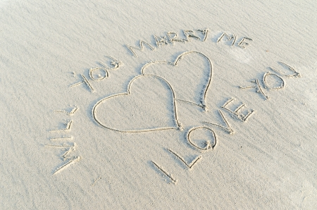 Heart drawn on sand with I love you and will you marry me text on it photo