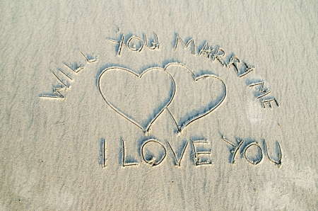 Heart drawn on sand with I love you and will you marry me text on it 版權商用圖片
