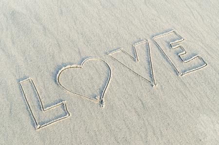 Hearts drawn with  love text on the sand of a beach photo