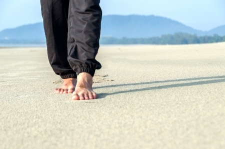 someone walking on the sand of a beach photo