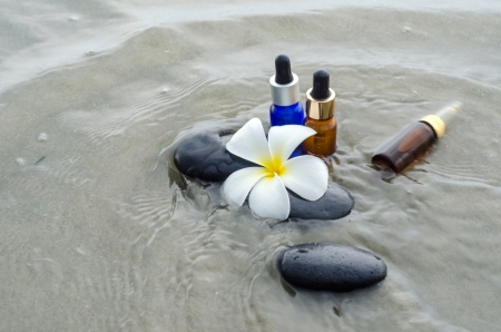 Essential oil with white frangipani flower and zen stones photo