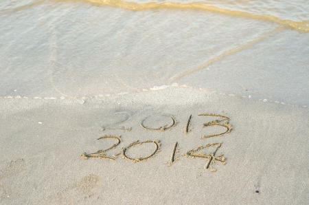 New Year 2014 is coming concept - inscription 2013 and 2014 on a beach sand photo