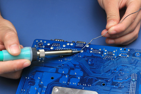 electronic circuit: Closeup of a technicians hands soldering a computer mainboard